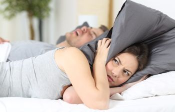 Woman in Bed With Pillow Over Her Head